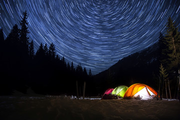 Night camp with illuminated tents in the mountain landscape with star trails in the sky