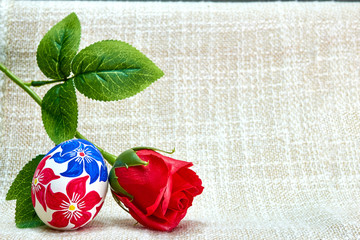 A rose flower near an easter egg hand-painted on a beautiful tablecloth