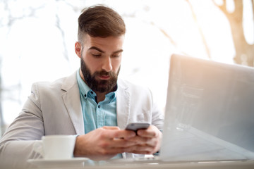 Handsome bearded man in stylish white and blue suit works on computer checking emails on smart phone.