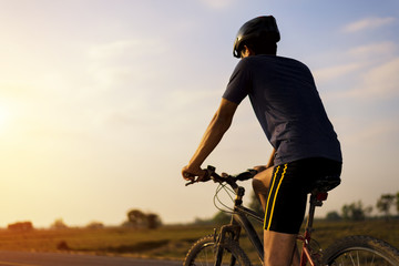 Rider is riding the bicycle on the road with sunset background. Exercise and health day.