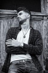 Young man posing behind wooden door