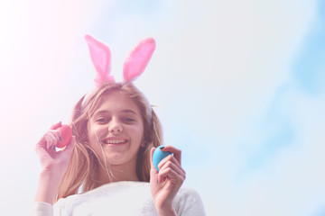 happy easter girl with bunny ears, eggs on blue sky