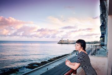 Young beautiful slender girl decollete dress balcony Malecon embankment El Morro fortress Havana Cuba Atlantic Ocean