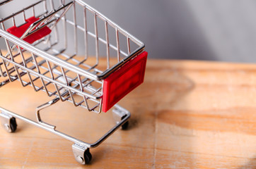 side view of Shopping cart on wood table ,shopping concept