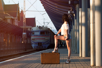 Lonely young brunette woman, in sexy shorts with old suitcase on station platform with sunlight