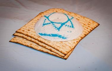 Three pieces of matzah with a Jewish cap kippah on the top. Jewish tradition illustrative image. Pesach, Jewish Passover stock image.