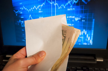 Hand holding envelope with money, stock exchange graph on the background. Stock exchange trading, insider trading stock image.
