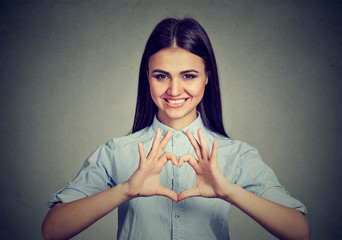Cheerful woman making heart sign with hands