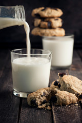 Two glasses of milk and cookies on the wooden table. Milk is poured into a glass. Black background. Selective focus.