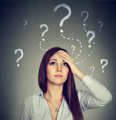 Woman with worried expression looking up has many questions