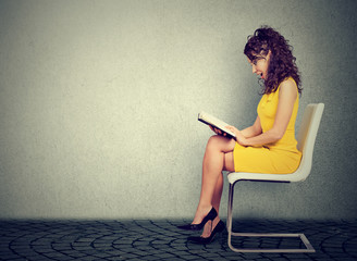 Young woman reading a book sitting on a chair