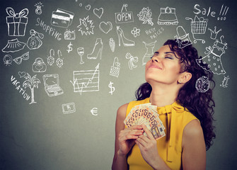 Young woman with money dreaming how to spend it all