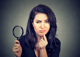 Curious young woman with magnifying glass