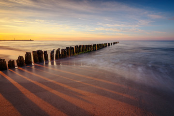 Beautiful sunset over Baltic sea with wooden breakwaters. Poland