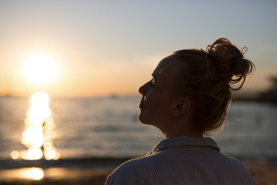 Sillouette of a woman with a bun enjoying the beautiful sunset.