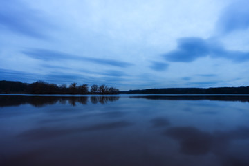 Late evening blue land and sky reflected like a mirror in calm lake, tranquil scene