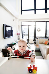 8 month old baby boy smiling and playing with toy at adult table in penthouse