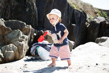 Baby boy playing on the beach with shovel