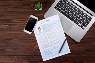Resume, phone and laptop on wooden table