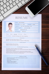 Resume, phone and keyboard on wooden table