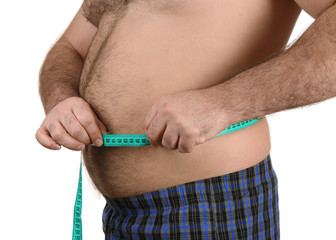 Man measuring beer belly on white background