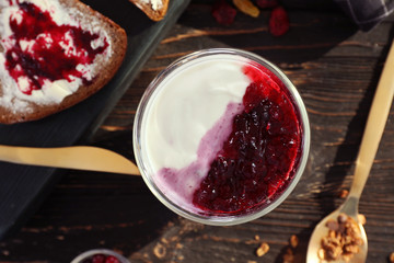 Delicious dessert with berry jam in glass on table