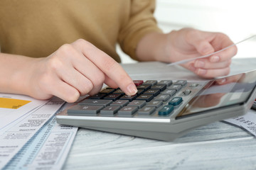 Woman sitting at table with calculator and bills
