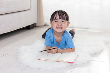 Happy Asian Chinese little girl lying on the floor drawing