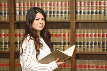 Young attractive female law student in law library