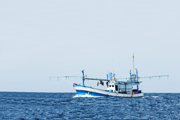 fishing boat in ocean against clear sky.