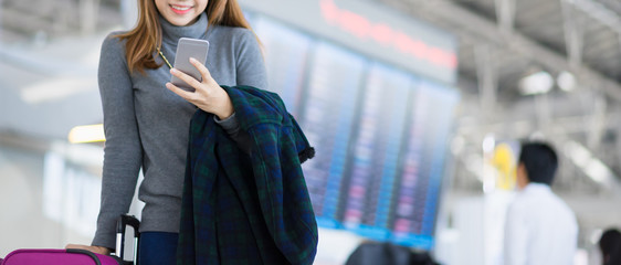 Charming beautiful business woman smile in casual style using smartphone and hold luggage bag for travel with blur the airport terminal.