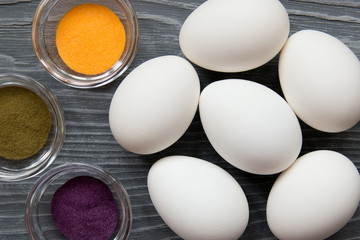 White chicken eggs and color pigments on a gray table. Celebrating Easter
