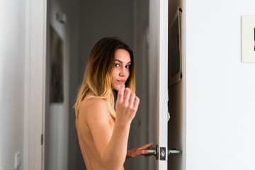 Topless young woman holding the door while looking at camera.