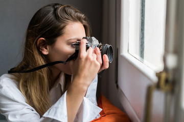 Woman with camera shooting window