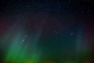 Aurora in the night sky with stars.