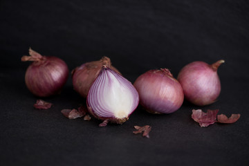 Full and half cut spanish onions on dark background.