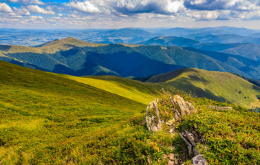 landscape with grassy meadow and giant boulders on the slope of a hill. Carpathian mountain ridge.  beautiful sunny summer day