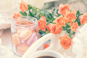 Cup of coffee. Orange mango or citrous macaroons and marshmallow in jars. Fresh little roses. Light wooden background. Sunlight. Toned photo with light vintage style. Shallow depth of field.