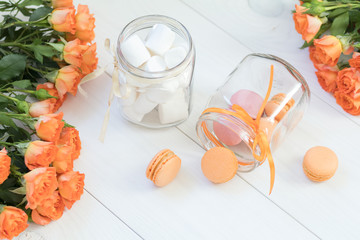 Orange mango or citrous macaroons and marshmallow in jars. Fresh little roses. Light wooden background. Sunlight. Coloring and processing photo with light vintage style. Shallow depth of field.