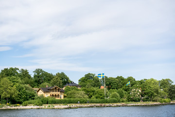 Coastal houses with Swedish flags and cycling people, on an island of Stockholm archipelago, peaceful view on a sunny summer day, Sweden