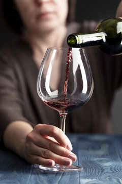 Alcoholic woman is pouring wine into a glass on kitchen