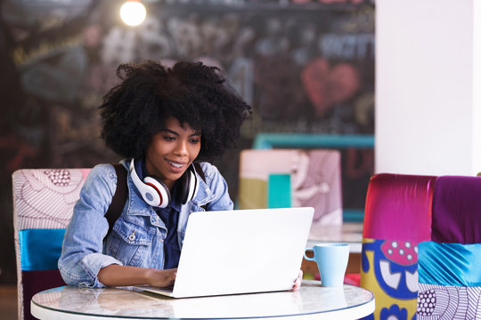 Beautiful young african american student girl with a lot of books and laptop