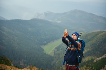 Young hiker taking a selfie from a mountain peak Wall mural