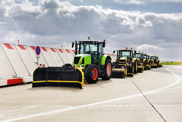 A column of empty harvesting equipment and tractors with buckets