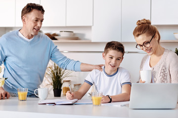 Positive parents helping his son with home assignment