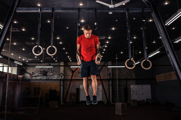 Athlete working out his muscles on rings