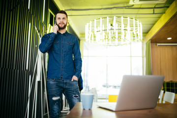 Handsome male entrepreneur standing at his desk and talking phone in office