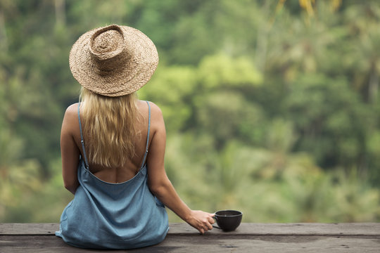 Rural woman with cup of coffee siting and look on jungle forest. Back view.