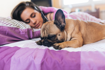 Attractive young woman sleeping on bed next to her french bulldog.