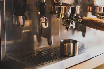 Barista using coffee shop machine pouring espresso shot in metal cup